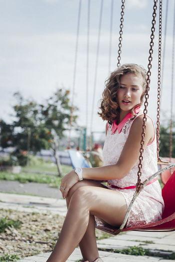 Girl sitting on swing at playground