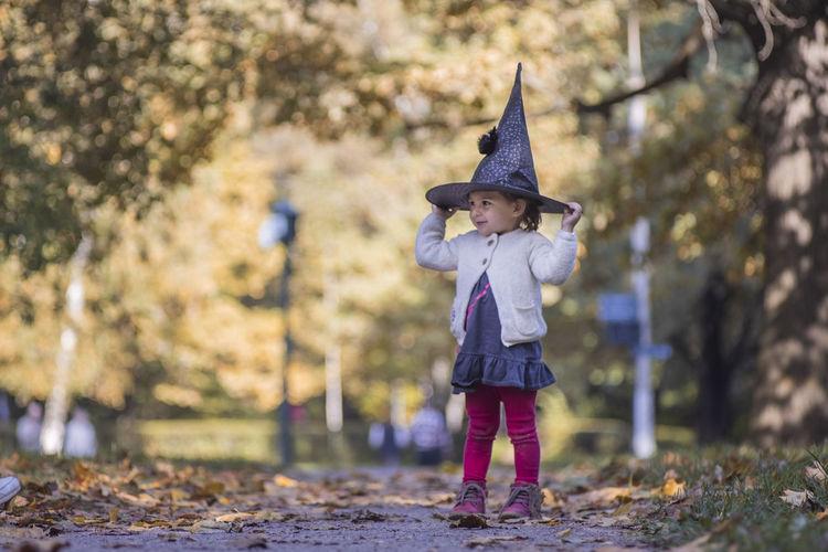Full length of girl wearing hat standing outdoors