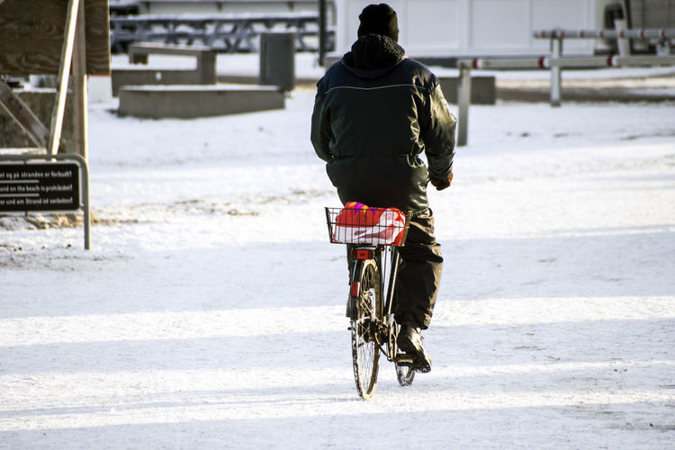 Elderly cyclist traveling on snow in denmark Bicycle Cold Temperature Full Length Fun Land Vehicle Leisure Activity Lifestyles Men Mode Of Transport Outdoors Real People Rear View Riding Stationary Street Togetherness Transportation Winter