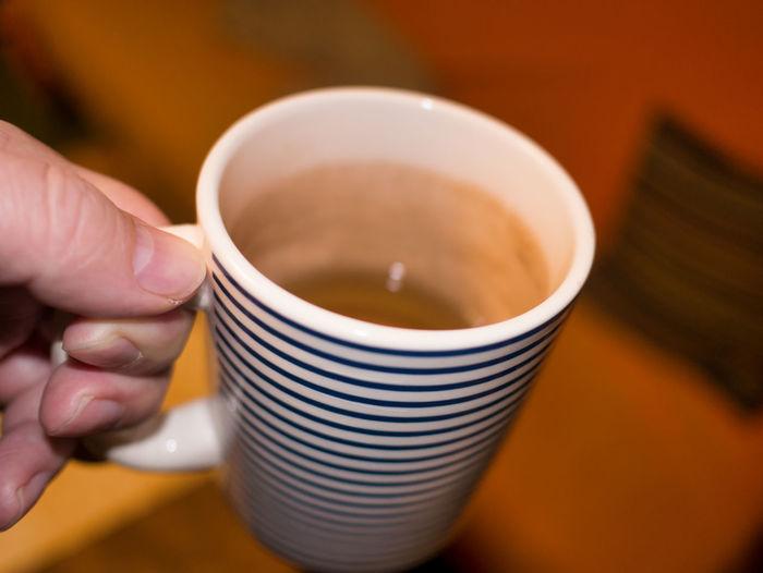 Close-up of hand holding a mug