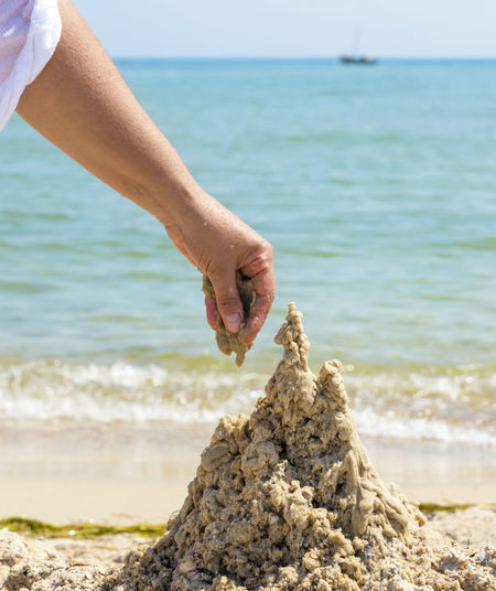 Cropped hand making sandcastle at beach