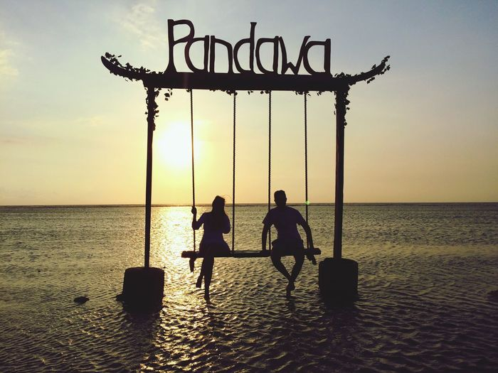 Silhouette couple sitting on swing in sea during sunset