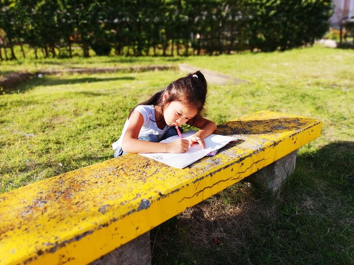 High angle view of girl doing homework on table while sitting in park