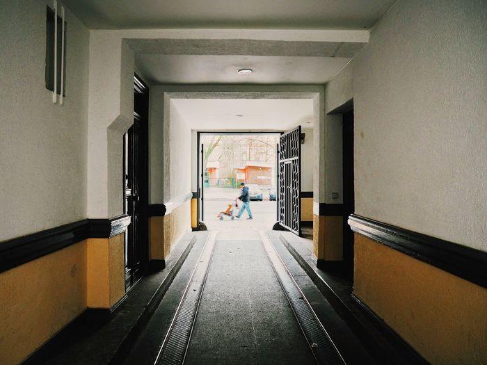 Man pushing baby in stroller seen through building corridor