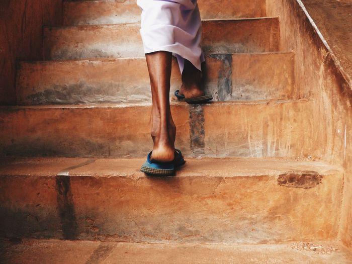 Low section of woman standing on staircase