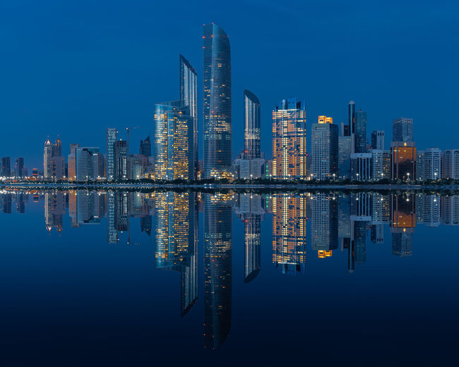 Reflection of illuminated buildings in lake against blue sky