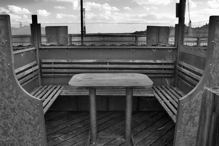 Empty chairs and tables against sky