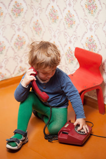 High Angle View Of Cute Boy Dialing On Rotary Phone At Home