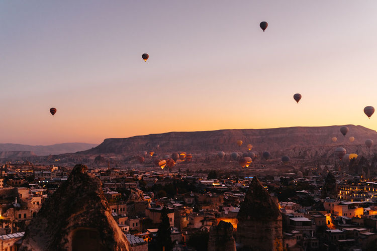 Hot air balloons in city against sky during sunset