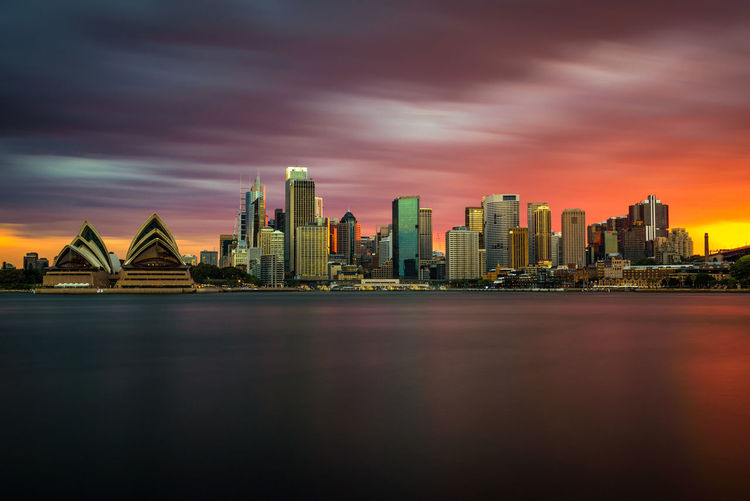 Illuminated city buildings against sky during sunset