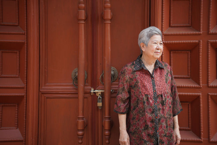 Senior woman standing against door