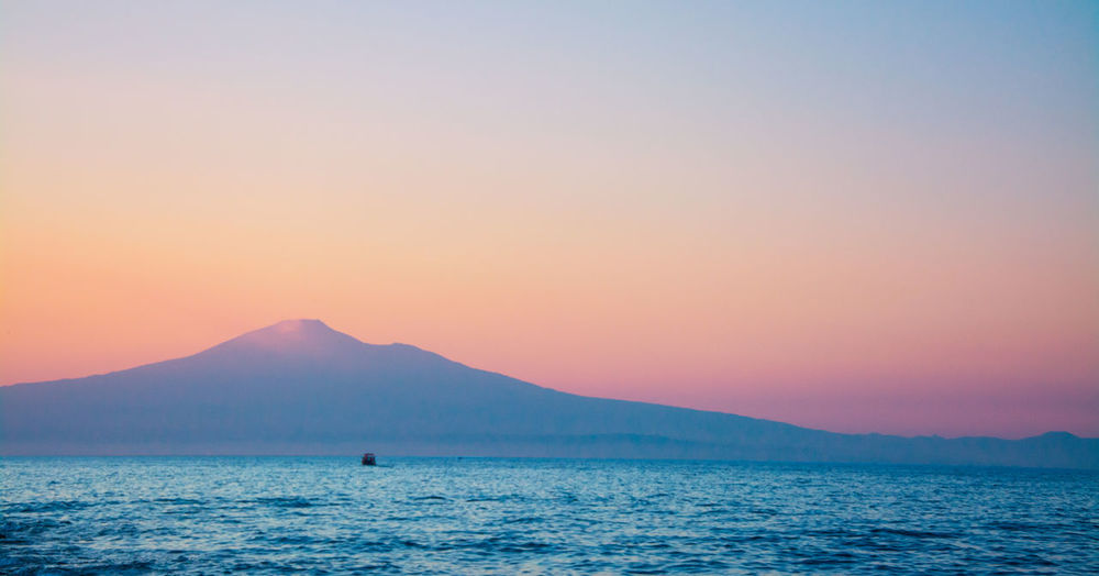 Scenic view of sea by mount etna against sky during sunset