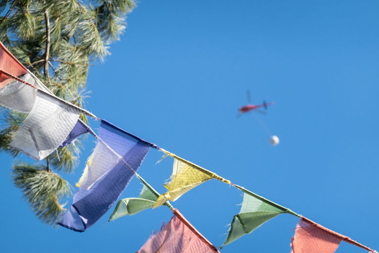 Low angle view of flags hanging against clear blue sky