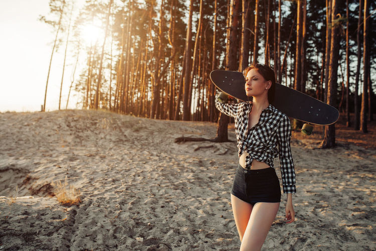 Woman With Skateboard Walking In Forest