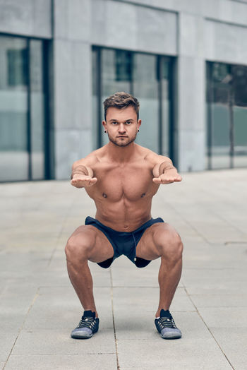 Young muscular man doing squats Athlete Athletic Body & Fitness Bodybuilding Exercising Lifestyle Man Squat Effort Exercising Fit Full Length Healthy Lifestyle Lifestyles Muscular Muscular Build One Person Real People Shirtless Shorts Sport Strength Workout