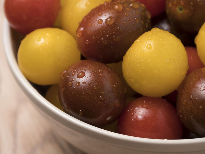 Cherry tomatoes in a variety of colors in ceramic bowl on wooden background. Fresh; Food; Healthy; Ripe; Red; Vegetable; Cherry; Tomato; Vegetarian; Yellow; Diet; Orange; Variety; Colorful; Different; Health; Green; Organic; Ingredient; Many; Summer; Small; Juicy; Raw; Nature; Tomatoes; Color; Natural; Closeup; Background; Agricul Food And Drink Food Freshness Close-up Still Life No People Indoors  Healthy Eating Fruit Wellbeing Bowl Olive High Angle View Large Group Of Objects Focus On Foreground Wet Ready-to-eat Water Indulgence Temptation