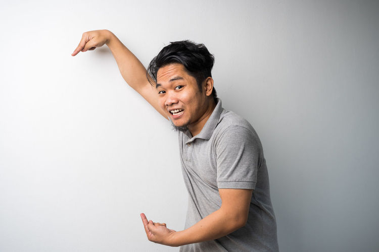Smiling young man standing against white background