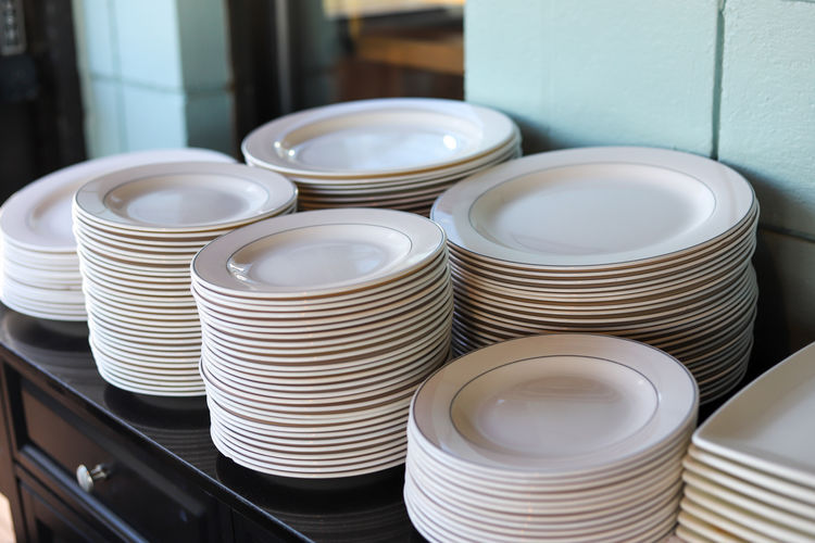 A stack of white dinner plates at a catered event