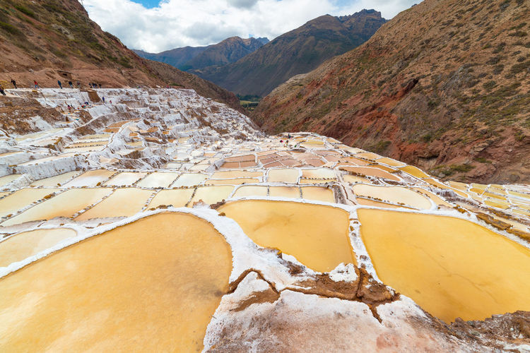 "White salt pans also known as ""Salineras de Maras"", among the most scenic travel destination in Cusco Region, Peru. Wide angle view from above with glowing water surfaces and salt ponds. Keywords: salt pan,pond,salt,Travel Destinations,maras,glowing,production,mineral,adventure,canal,drain,sewer,white,andes,dramatic,sky,terraces,flowing,sunlight,water,exploration,Landscape,geothermal,beauty,shape,contrasts,mine,valley,landscaped,cusco,channel,geometric,evaporation,basin,south america,peru,landmark,Panoramic,travel,mountain,outdoors,remote,Scenics,Majestic,Idyllic,above,wide-angle,nobody,reflection Arid Climate Beauty In Nature Curve Day Geology Hot Spring Landscape Mountain Mountain Range Nature No People Outdoors Physical Geography Rock - Object Salt - Mineral Scenics Sky Tranquil Scene Tranquility Travel Destinations Winding Road"