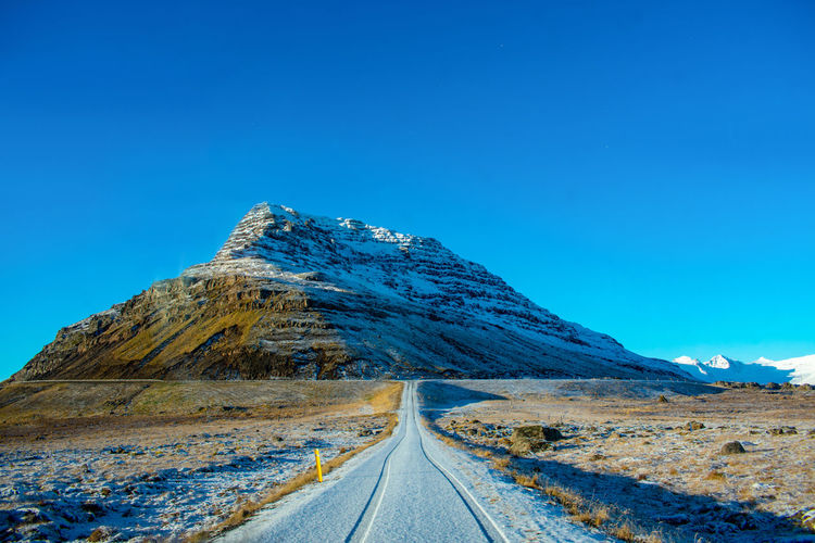 Empty Road Leading Towards Mountain Against Clear Blue Sky