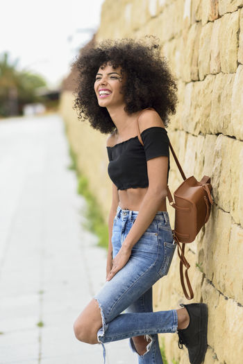 Mid Adult Woman With Curly Hair Standing Against Wall