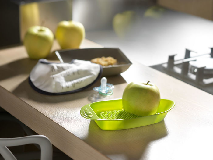 Green apple and pacifier on table
