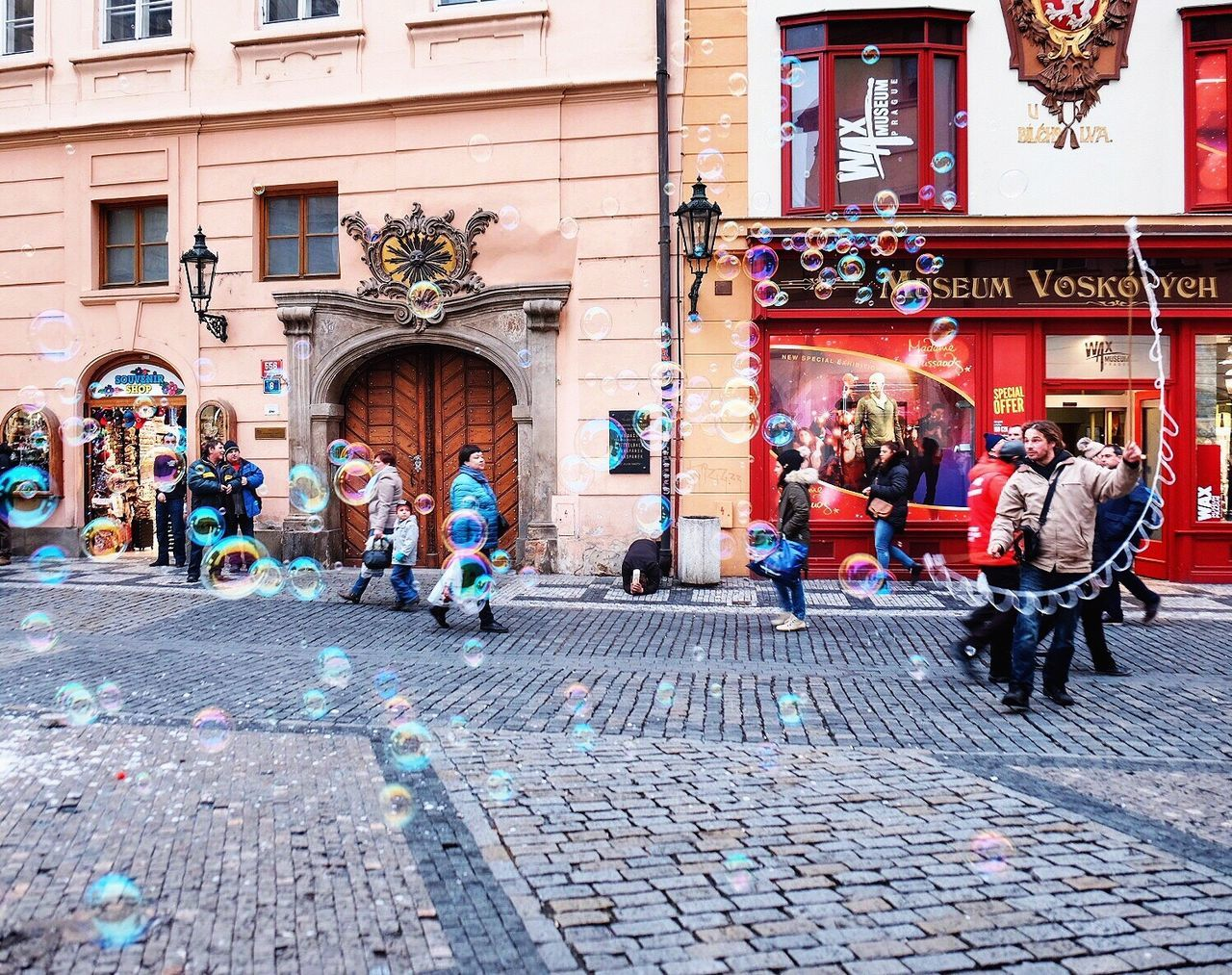 architecture, cobblestone, building exterior, street, real people, built structure, outdoors, men, large group of people, day, city, people