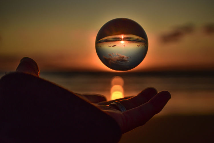 Man hand holding crystal ball against sea during sunset