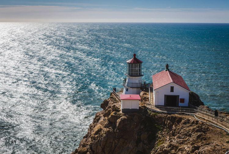 Lighthouse and sea against sky