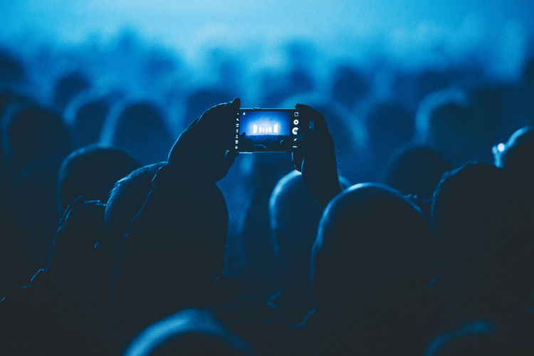 Man In Crowd Photographing Illuminated Stage Through Smart Phone At Theater