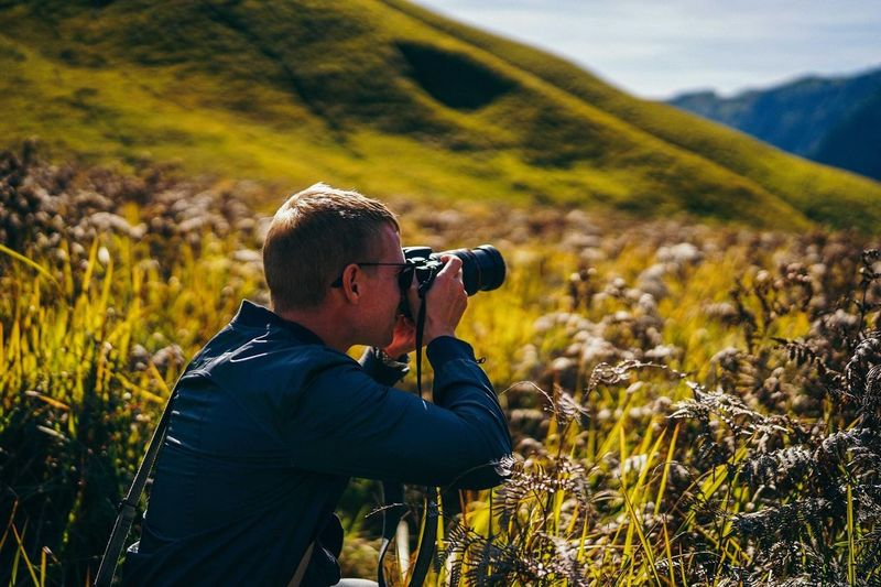 Side view of man photographing with camera while standing on grassy field