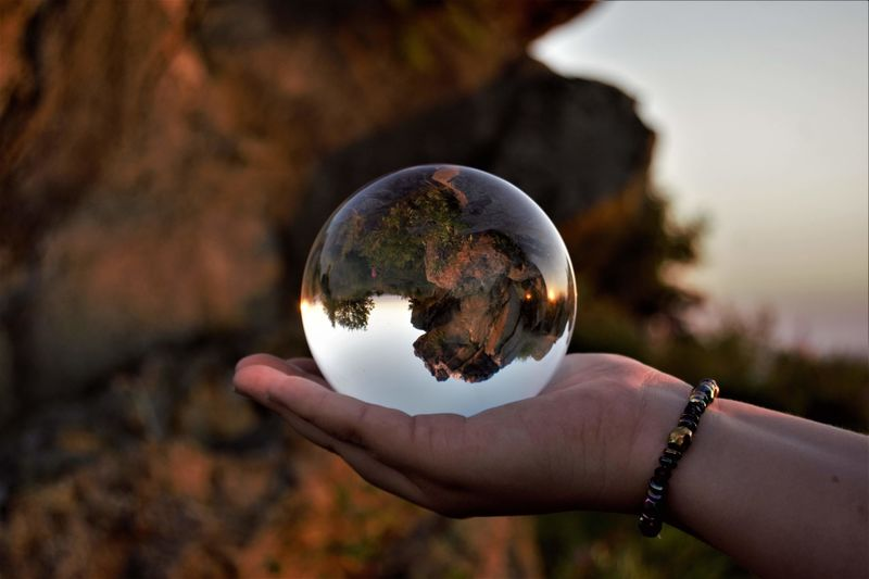 Close-up of hand holding crystal ball outdoors