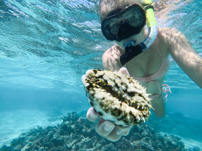 Close-up of woman snorkeling while holding coral undersea