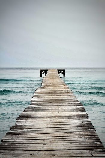 Jetty Leading To Calm Sea Against Clear Sky