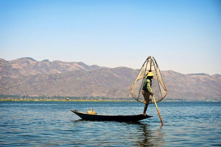 Man in boat on lake against mountain range