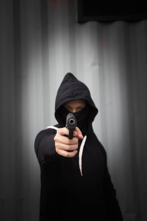 Criminal man pulling out a gun ready to shoot Crime Dark Murder Stolen Stress Addict Attack Of The Macro Collection! Carry Crime Danger Defense Front View Gangster Gun Handgun Headshot Holding Hood - Clothing Hooded Shirt Kill Mafia  One Person Robber THREATS Weapon