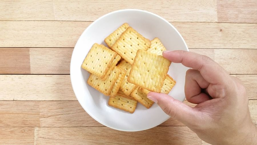 Hand Holds Homemade Crackers on Wood Table White Dishes Breakfast Morning Dessert Crackers Morning Breakfast Yellow Food And Drink Foodphotography Wood Wood Table Table Mobilephotography Handmade Hand Hand Holding