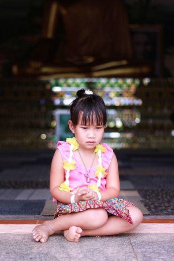 Thoughtful girl sitting on floor