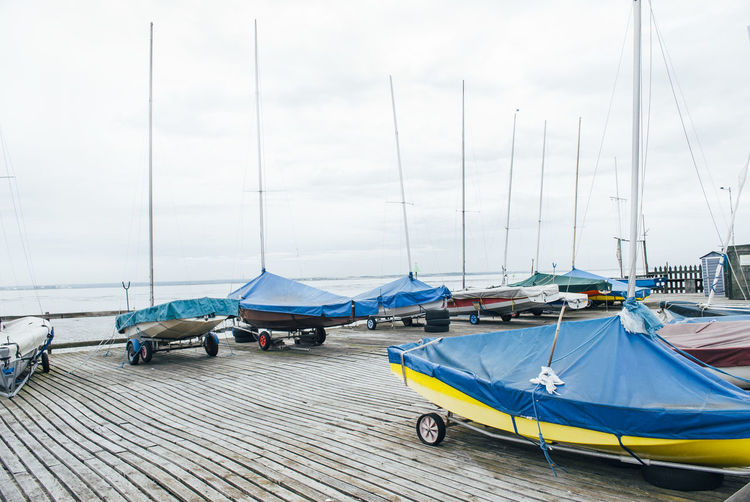 Boats moored promenade by sea against cloudy sky