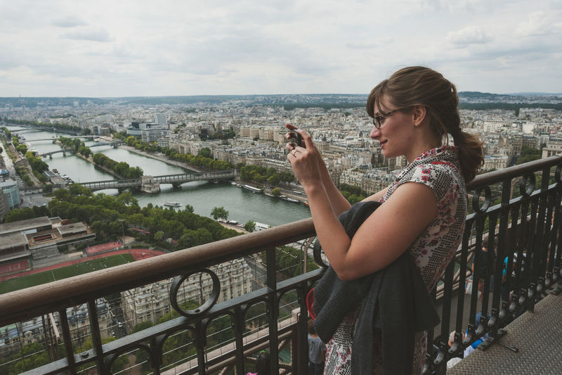 Woman photographing on mobile phone while standing by railing against sky