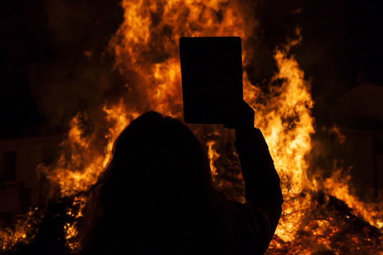 Rear view of silhouette woman standing with book against bonfire at night