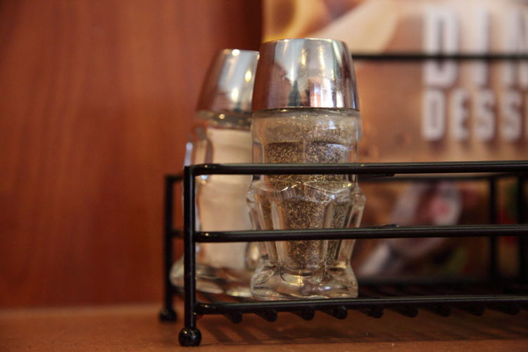 Close-up of salt and pepper shakers in metal container on table