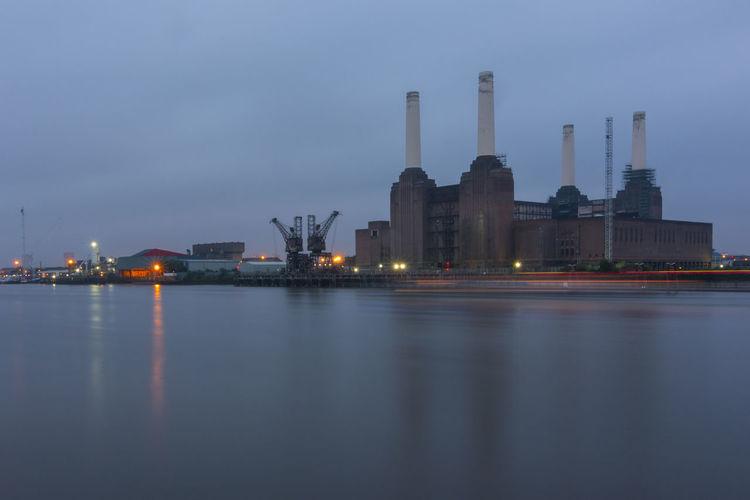 Illuminated Factory By Lake At Dusk