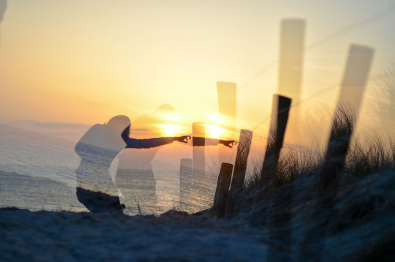 Digital composite image of sea against sky during sunset