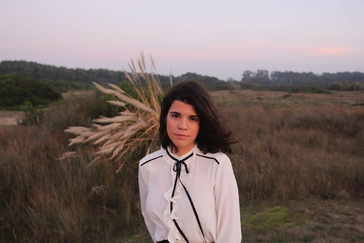 Portrait Of Beautiful Young Woman Standing On Field Against Sky During Sunset