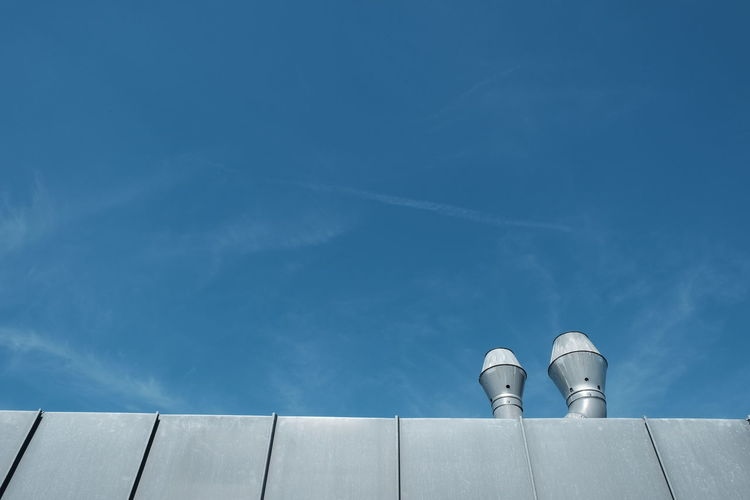 Low Angle View Of Smoke Stacks On Roof Against Blue Sky