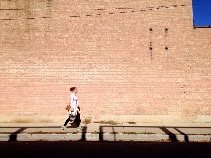 Full length of woman walking on brick wall