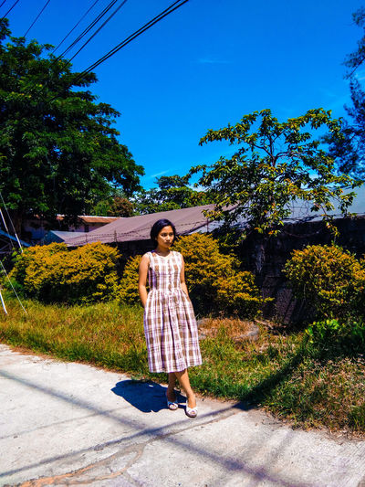 Full length of young woman looking away while standing on footpath against blue sky
