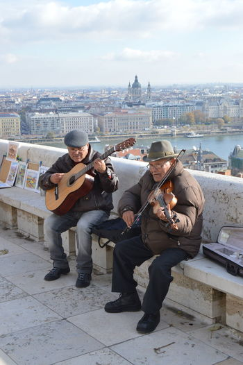 Old street musicians playing up above the city, bring positive energy to tourists while sightseeing the city's panorama, and making money for life. Arhitecture Cityscape Hungary Old Man Playing Guitar Sightseeing Travel Art Budapest Panorama City Cityscape Day Earning For Living Full Length Men Musical Instrument Musician Old Musician Outdoors Playing Violin Real People Sky Street Musicians Traveling Photography Urban Skyline