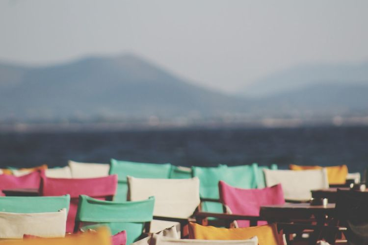 Multi colored chairs at beach against sky